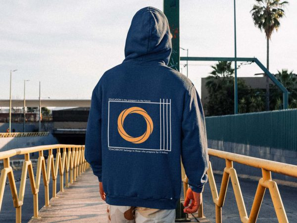back view knowledge hoodie of a man standing on a city street