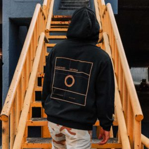 back view of a man wearing a badge hoodie and on a metal staircase