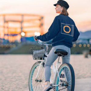 young woman with a knowledge sweatshirt riding a bike